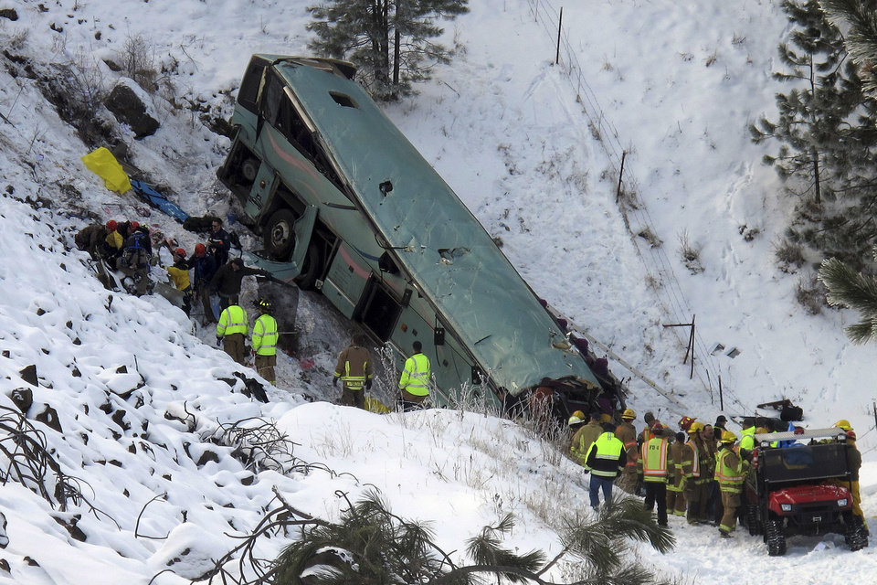 Photo - Emergency personnel respond to the scene of a multiple-fatality accident after a tour bus careened through a guardrail along an icy highway and fell several hundred feet down a steep embankment, authorities said, Sunday, Dec. 30, 2012 about 15 miles east of Pendleton, Ore. The charter bus carrying about 40 people lost control around 10:30 a.m. on the snow- and ice-covered lanes of Interstate 84, according to the Oregon State Police. (AP Photo/East Oregonian, Tim Trainor)