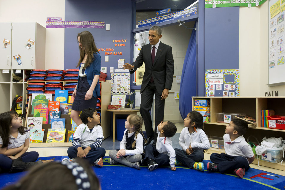 Photo - President Barack Obama waves to preschool students as he follows teacher Laura Steinmetz during his visit to the classroom at Powell Elementary School in the Petworth neighborhood of Washington, Tuesday, March 4, 2014.  Obama visited the school to talk about his fiscal 2015 budget proposal, which was released today. Powell elementary has seen rapid growth in recent years and serves a predominantly Hispanic student body. Washington DC Mayor Vincent Gray, who greeted Obama at the school, recently directed $20 million to Powell for a planned modernization and addition. (AP Photo/Pablo Martinez Monsivais)