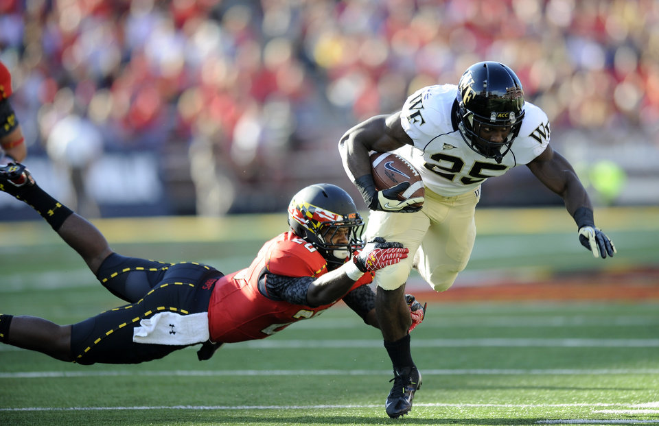 Wake Forest running back Josh Harris (25) runs with the ball against Maryland defensive back Anthony Nixon, left, during the first half of an NCAA football game, Saturday, Oct. 6, 2012, in College Park, Md. (AP Photo/Nick Wass)