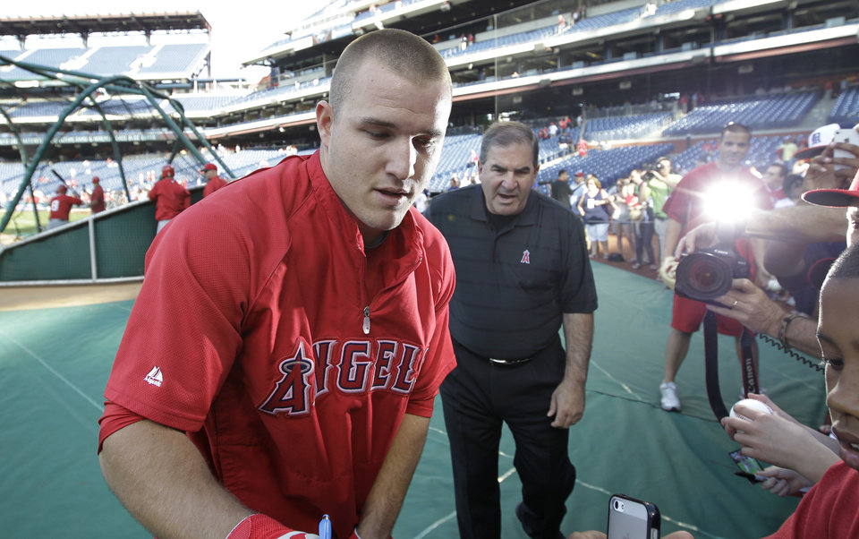 Photo - Los Angeles Angels' Mike Trout signs autographs before the start of a baseball game with the Philadelphia Phillies, Tuesday, May 13, 2014, in Philadelphia. (AP Photo/Laurence Kesterson)