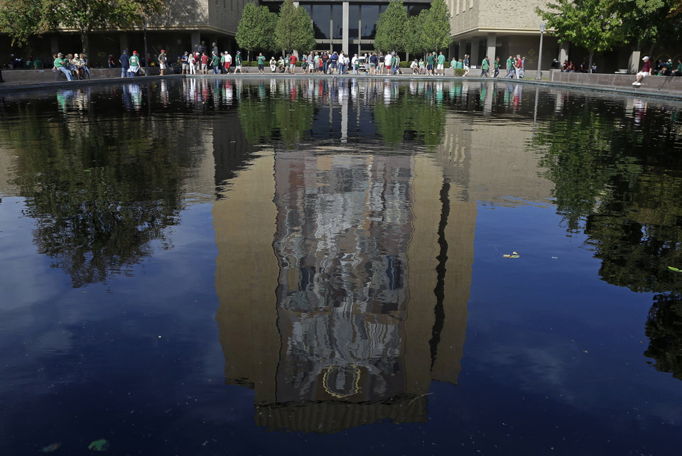"""Photo - A mosaic-mural titled """"Word of Life"""" on the facade of the Hesburgh Library is reflected in a pool as fans walk past before the start of an NCAA college football game between Notre Dame and Oklahoma Saturday, Sept. 28, 2013, in South Bend, Ind. The mural is also know as """"Touchdown Jesus"""" in which He seems to be signalling six points. (AP Photo/Darron Cummings)  ORG XMIT: INDC101"""