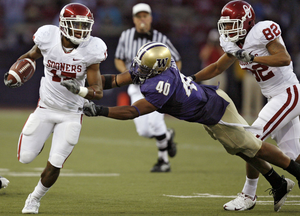 Photo - Oklahoma's Mossis Madu (17) runs past a tackle attempt by Washington's Mason Foster (40) during the second half of the college football game between the University of Oklahoma Sooners (OU) and the University of Washington Huskies (UW) at Husky Stadium on Saturday, Sep. 13, 2008, in Seattle, Wash. 
