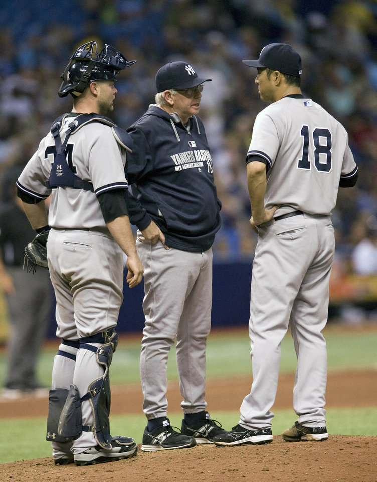 Photo - New York Yankees pitching coach Larry Rothschild, center, talks with catcher Brian McCann, left, and pitcher Hiroki Kuroda (18) during the sixth inning of a baseball game against the Tampa Bay Rays, Friday, April 18, 2014, in St. Petersburg, Fla. (AP Photo/Steve Nesius)