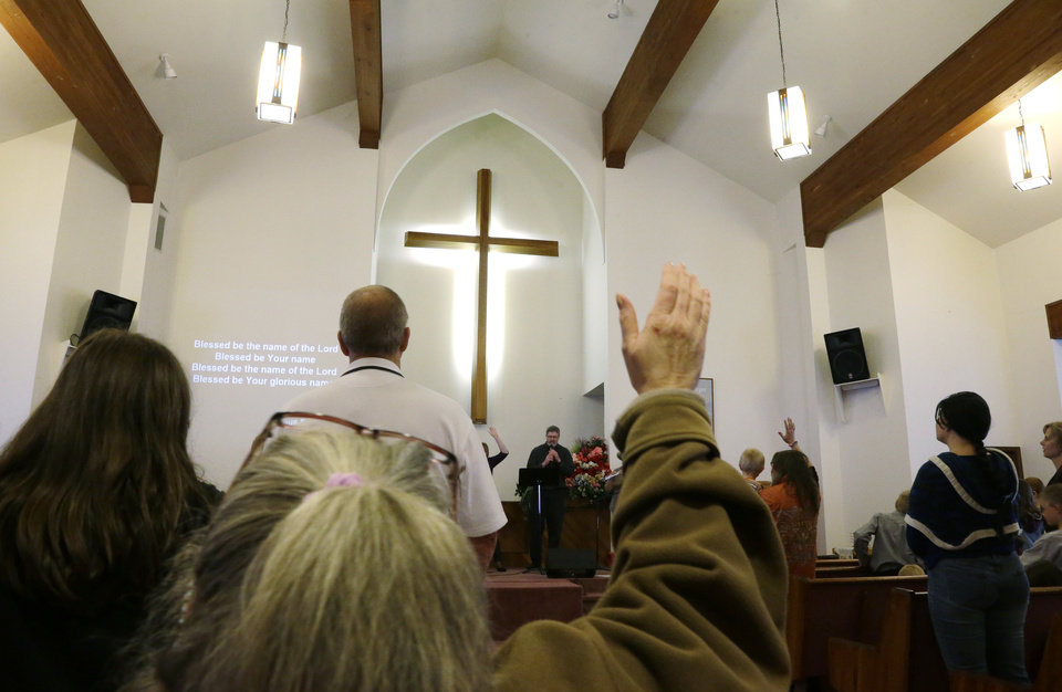 Photo - A member of the congregation at Glad Tidings Assembly of God church in Darrington, Wash., raises her hand as she sings Sunday, March 30, 2014 during morning church services. Much of the music and speaking was devoted to reaction to the deadly mudslide that hit the nearby community of Oso, Wash. on Saturday, March 22, 2014. (AP Photo/Ted S. Warren)