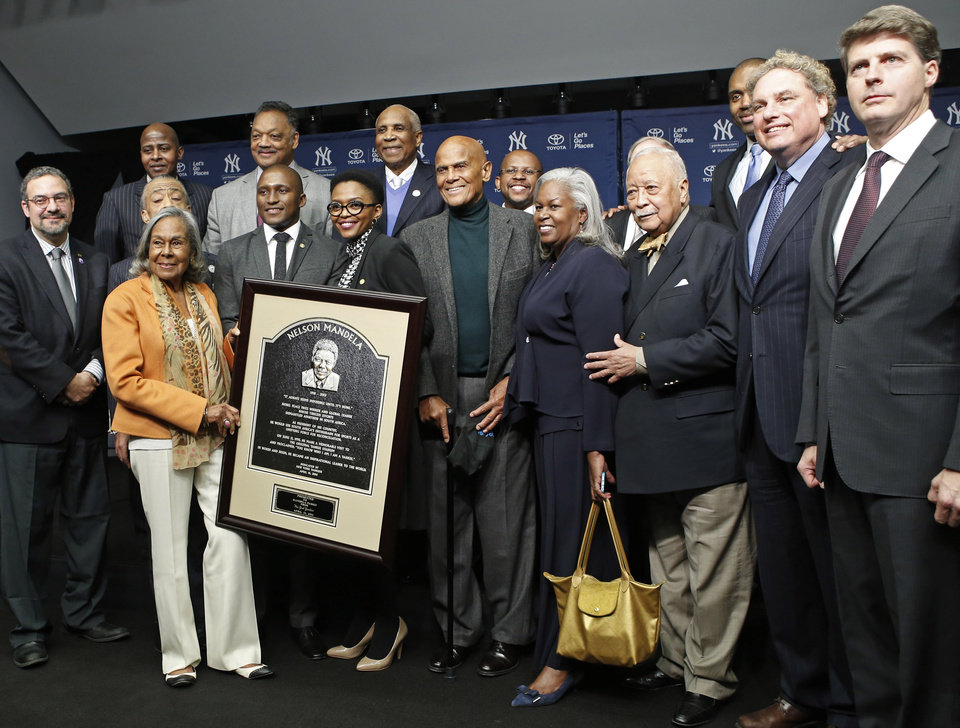Photo - Dignitaries pose with a photo of a plaque honoring former South African President Nelson Mandela to be unveiled on Wednesday, April 16, 2014, in Yankee Stadium's Monument Park in New York. Front row, from left, Jackie Robinson's widow Rachel Robinson, Nelson Mandela's grandson Zondwa Mandela, his wife Lindo Mandela, singer and civil rights activist Harry Belafonte, Jackie Robinson's daughter Sharon Robinson, former New York Mayor David Dinkins, New York Yankees President Randy Levine and Yankees owner Hal Steinbrenner join Rev. Jesse Jackson, rear, third from left, former MLB manager Frank Robinson, back row, fourth from left, and others before Game 2 of a baseball doubleheader between the Yankees and the Chicago Cubs at Yankee Stadium. (AP Photo/Kathy Willens)