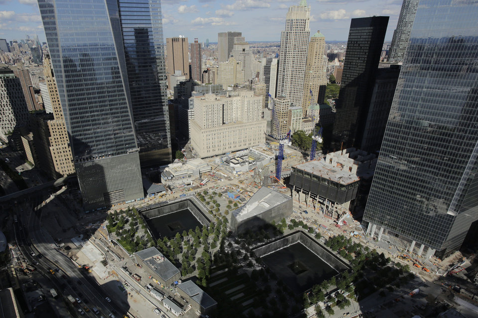 Photo - In this photo taken Thursday, Sept. 5, 2013, the wedge-shaped pavilion entrance of the National September 11 Museum, center, is located between the square outlines of the memorial waterfalls at the World Trade Center in New York. Construction is racing ahead inside the museum as the 12th anniversary of the Sept. 11, 2001 attacks draws near. Several more large artifacts have been installed in the cavernous space below the World Trade Center memorial plaza.  (AP Photo/Mark Lennihan)