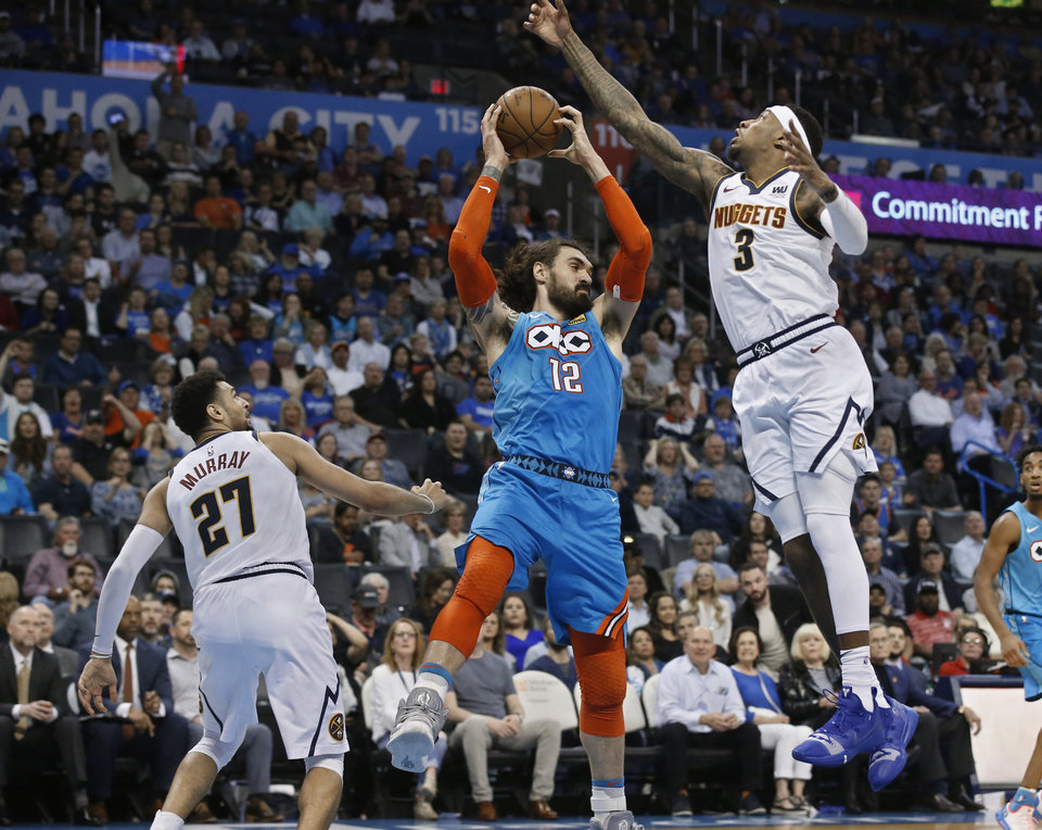 Photo - Oklahoma City Thunder center Steven Adams (12) grabs a rebound between Denver Nuggets guard Jamal Murray (27) and forward Torrey Craig (3) during the second half of an NBA basketball game Friday, March 29, 2019, in Oklahoma City. (AP Photo/Sue Ogrocki)