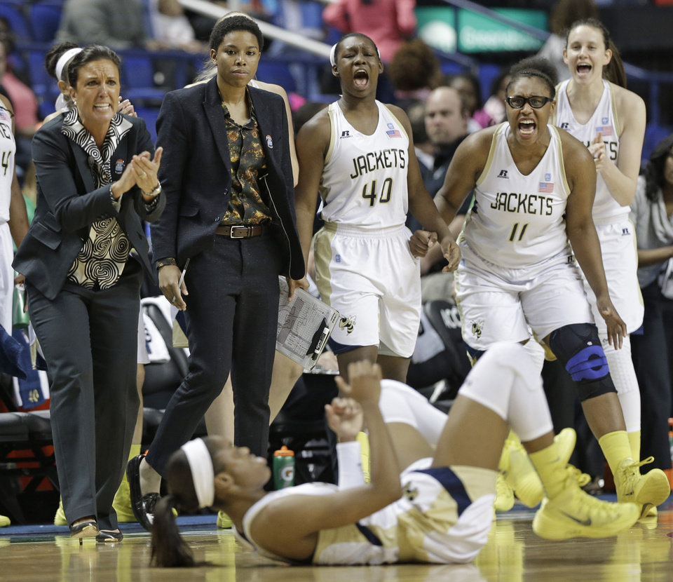 Photo - Georgia Tech head coach MaChelle Joseph, left, and players Nariah Taylor (11), and Gabrielle Holston (40) react after teammate Kaela Davis, front, is fouled after making a 3-point shot against Virginia during the second half of an NCAA college basketball game at the Atlantic Coast Conference tournament in Greensboro, N.C., Thursday, March 6, 2014. Georgia Tech won 77-76. (AP Photo/Chuck Burton)