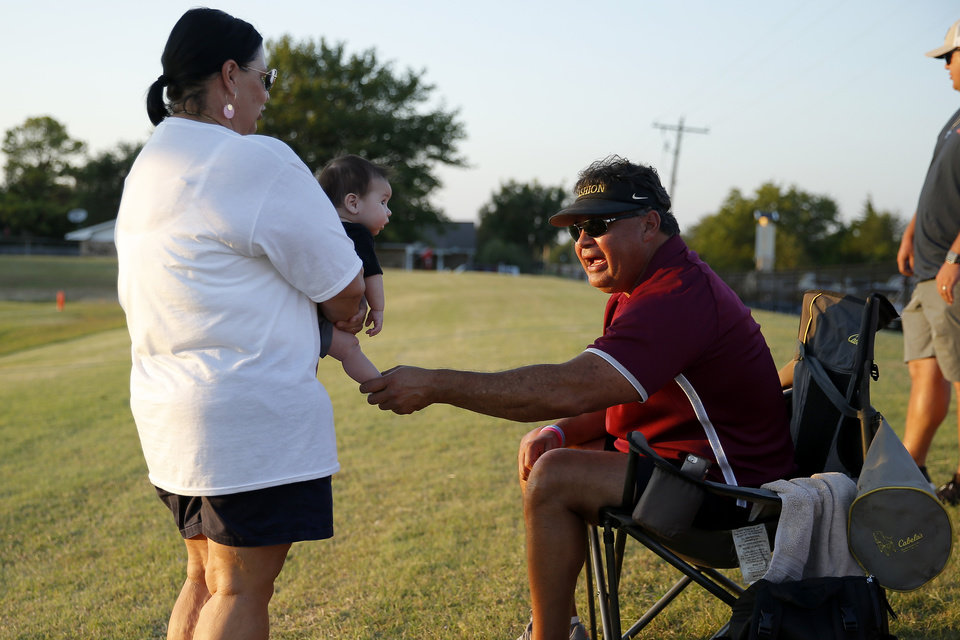 Photo - Lea Ann Stephens holds her grandson, Jaxon Cochran, while she talks with Chris Cochran, Jaxon's grandfather, during halftime of a high school football game between Cashion and Perry in Cashion, Okla., Friday, Sept. 4, 2020. Lea Ann Stephens' daughter Jacie Cochran died July 2 shortly after giving birth to Jaxon. [Bryan Terry/The Oklahoman]