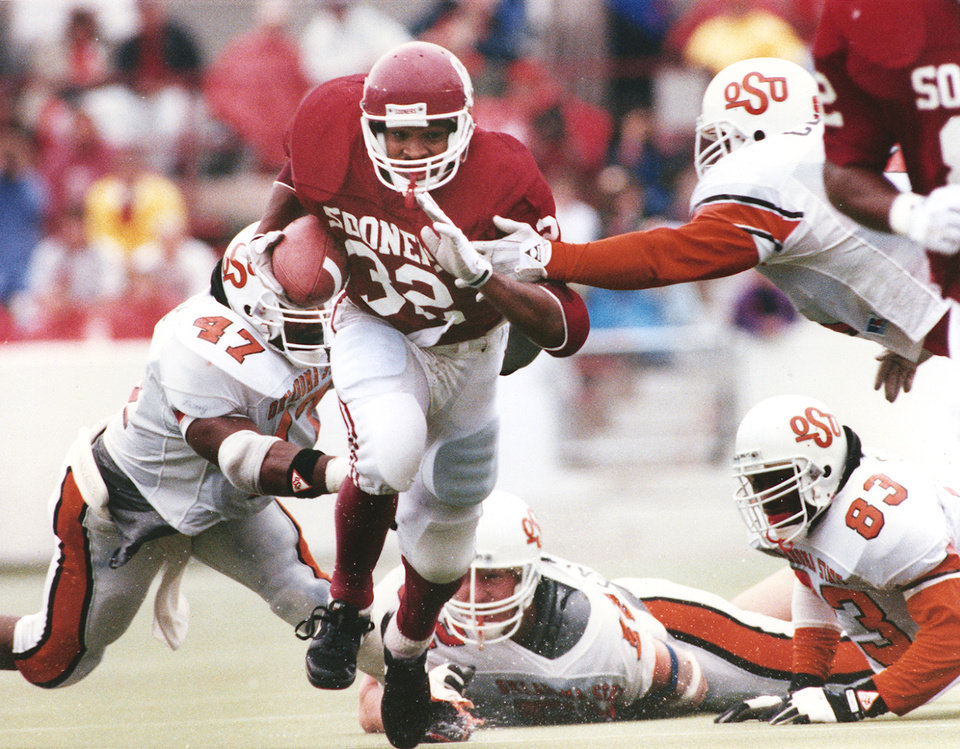 Photo - University of Oklahoma running back Mike Gaddis, center, runs past the outstretched arms of Oklahoma State University (OSU) defenders during the 1991 Bedlam college football game in Norman. The former Carl Albert High School standout ran for 203 yards on 35 carries on a rain-soaked Owen Field as the Sooners trimmed the Cowboys, 21-6. Gaddis, that day, became the first OU back to have consecutive 200-yard games since Billy Sims in 1979; Gaddis also surpassed the 1,000-yard mark on the season, the first Sooner to do that since Spencer Tillman in 1983. Photo from The Oklahoman Archives