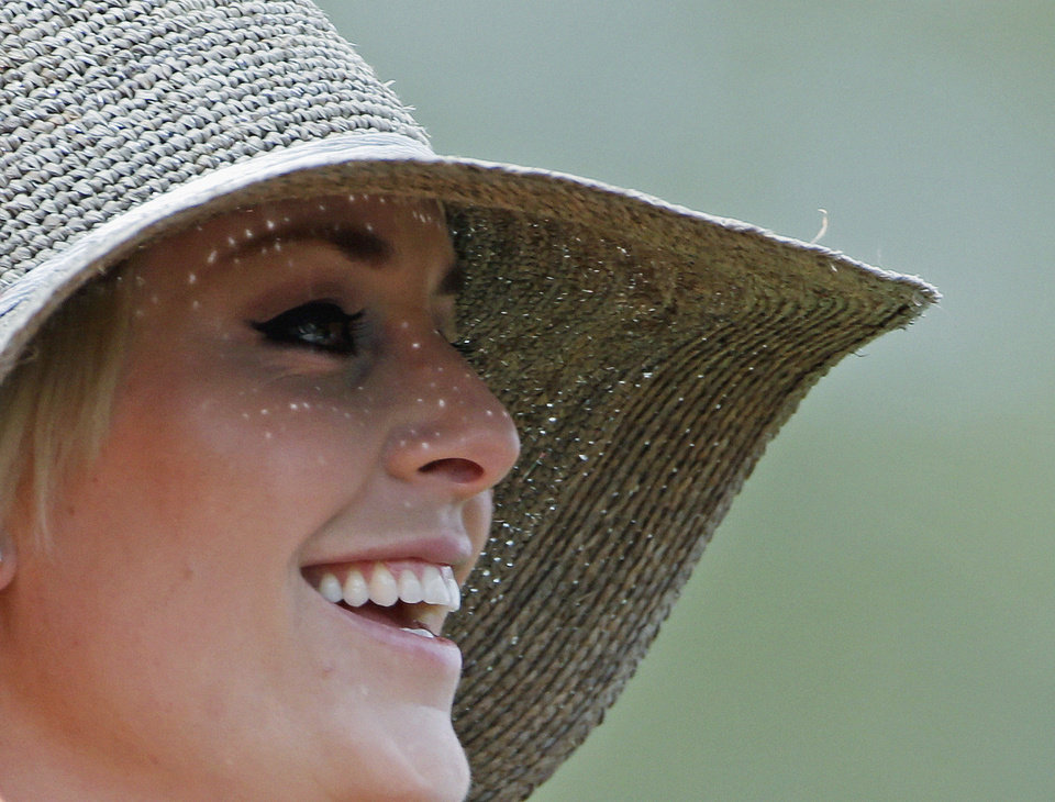 Photo - Skier Lindsey Vonn smiles as she watches Tiger Woods during the first round of the Masters golf tournament Thursday, April 11, 2013, in Augusta, Ga. (AP Photo/Darron Cummings)