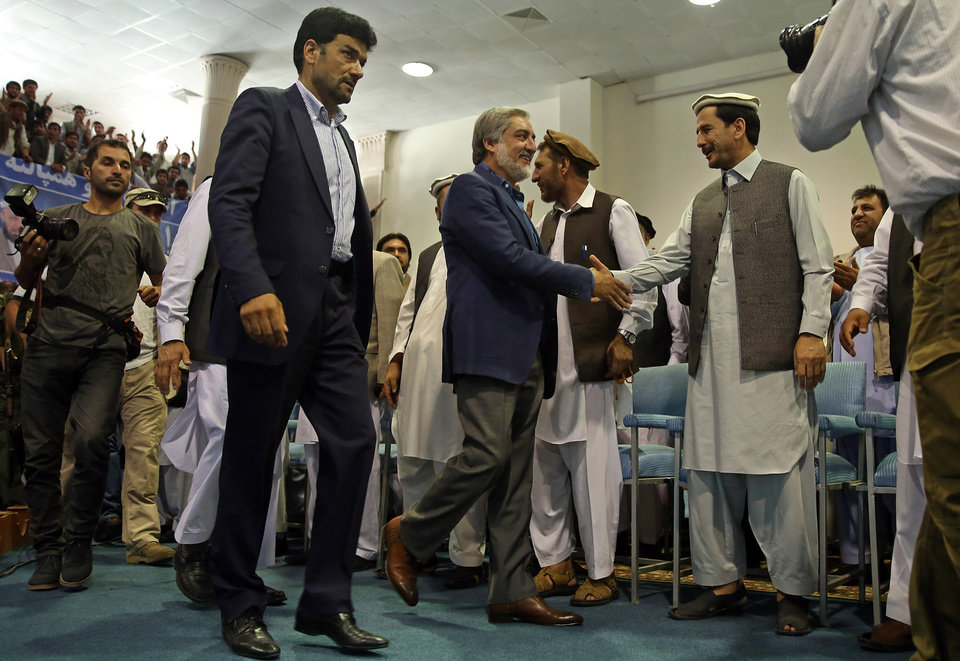 Photo - Afghanistan's presidential candidate Abdullah Abdullah, center, shakes hands as he arrives to a gathering of his supporters in Kabul, Afghanistan, Tuesday, July 8, 2014.  Abdullah on Tuesday said he received calls from President Barack Obama and U.S. Secretary of State John Kerry after he refused to accept the preliminary result of the vote citing fraud. Abdullah told thousands of supporters at a gathering in Kabul that Kerry would be flying to the Afghan capital this Friday for meetings and help defuse the crisis. (AP Photo/Massoud Hossaini)
