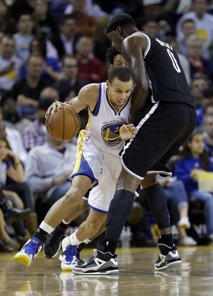 Golden State Warriors\' Stephen Curry, left, tries to dribble around Brooklyn Nets\' Andray Blatche (0) during the first half of an NBA basketball game in Oakland, Calif., Wednesday, Nov. 21, 2012. (AP Photo/Marcio Jose Sanchez)