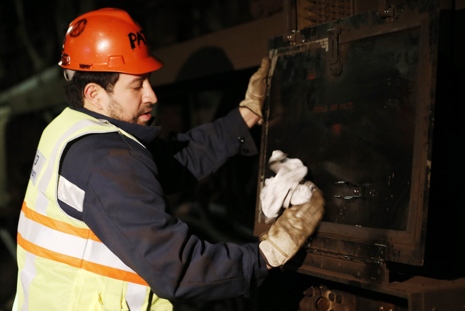 Photo -   Mauricio Lopez, power railman for the PATH train system, cleans up a panel damaged by Superstorm Sandy, Tuesday, Nov. 27, 2012, in Hoboken, N.J. While other parts of the trans-Hudson service have gradually been restored since the storm, the Hoboken station has been closed, leaving thousands of commuters to seek alternatives. (AP Photo/Julio Cortez)