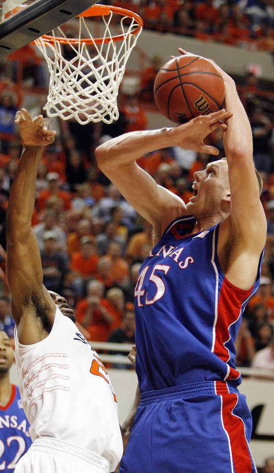 Photo - KU's Cole Aldrich (45) tries to keep control of the ball next to OSU's James Anderson (23) in the second half during the men's college basketball game between the University of Kansas (KU) and Oklahoma State University (OSU) at Gallagher-Iba Arena in Stillwater, Okla., Saturday, Feb. 27, 2010. OSU won, 85-77. Photo by Nate Billings, The Oklahoman