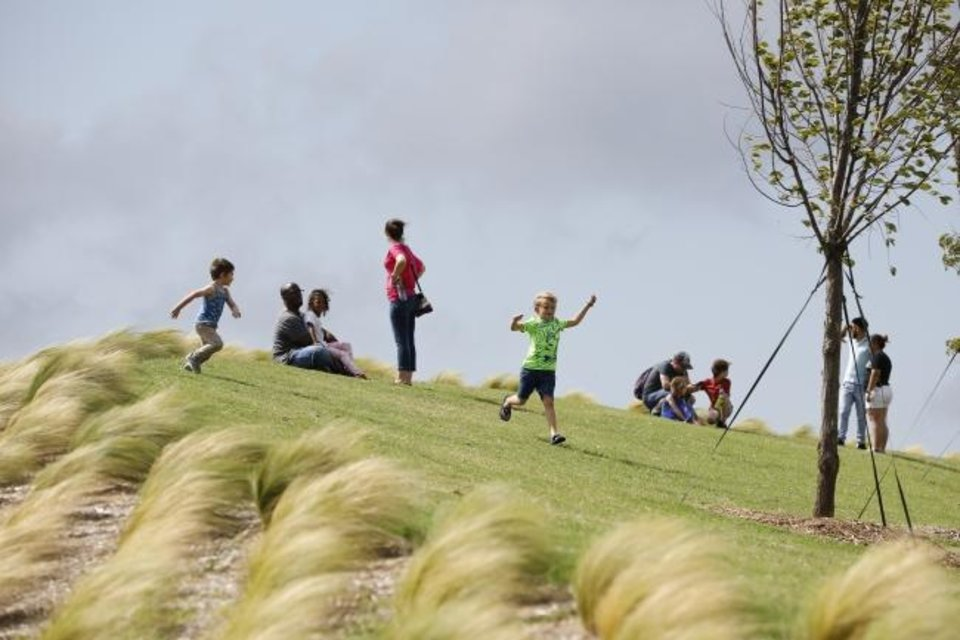 Photo -  People enjoy the hill at the great lawn Sunday during the grand opening weekend of Scissortail Park. [Alonzo Adams for The Oklahoman]
