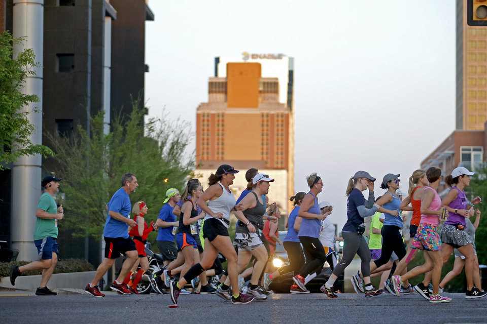 Photo - Runners make their way north Walnut Ave. during the Oklahoma City Memorial Marathon in Oklahoma City, Sunday, April 29, 2018. Photo by Bryan Terry, The Oklahoman