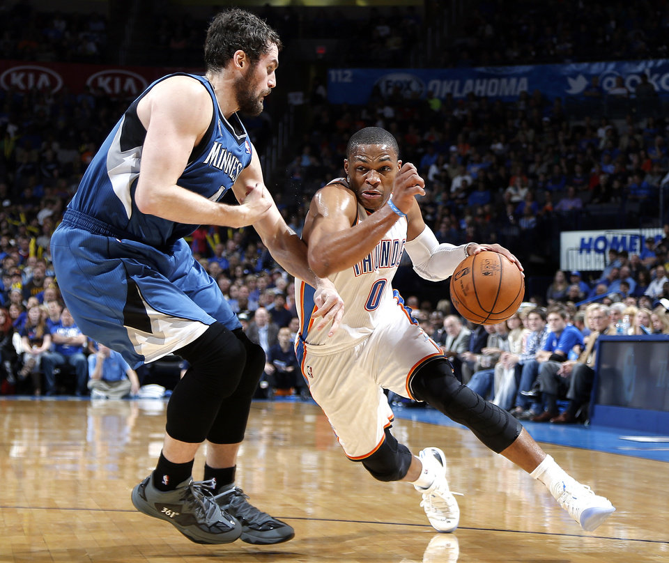 Photo - Oklahoma City's Russell Westbrook (0) drives past Minnesota's Kevin Love (42) during the NBA game between the Oklahoma City Thunder and the Minnesota Timberwolves at the Chesapeake Energy Arena, Sunday, Dec. 1, 2013. Photo by Sarah Phipps, The Oklahoman