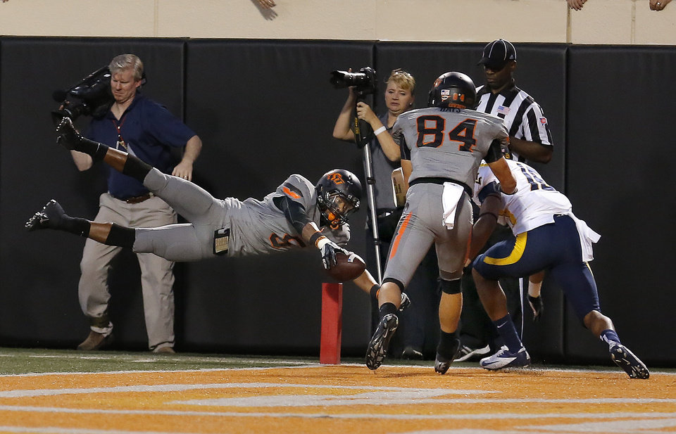 Photo - Oklahoma State's Josh Stewart (5) dives for a touchdown in the fourth quarter during a college football game between Oklahoma State University (OSU) and the West Virginia University at Boone Pickens Stadium in Stillwater, Okla., Saturday, Nov. 10, 2012. Photo by Sarah Phipps, The Oklahoman