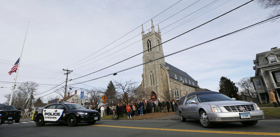 Photo - A hearse bearing the body of Benjamin Andrew Wheeler, one of the students killed in the Sandy Hook Elementary School shooting last week, leaves Trinity Episcopal Church after funeral services, Thursday, Dec. 20, 2012, in Newtown, Conn. Wheeler, 6, died when the gunman, Adam Lanza, walked into Sandy Hook Elementary School in Newtown, Dec. 14, and opened fire, killing 26 people, including 20 children, before killing himself. (AP Photo/Julio Cortez)