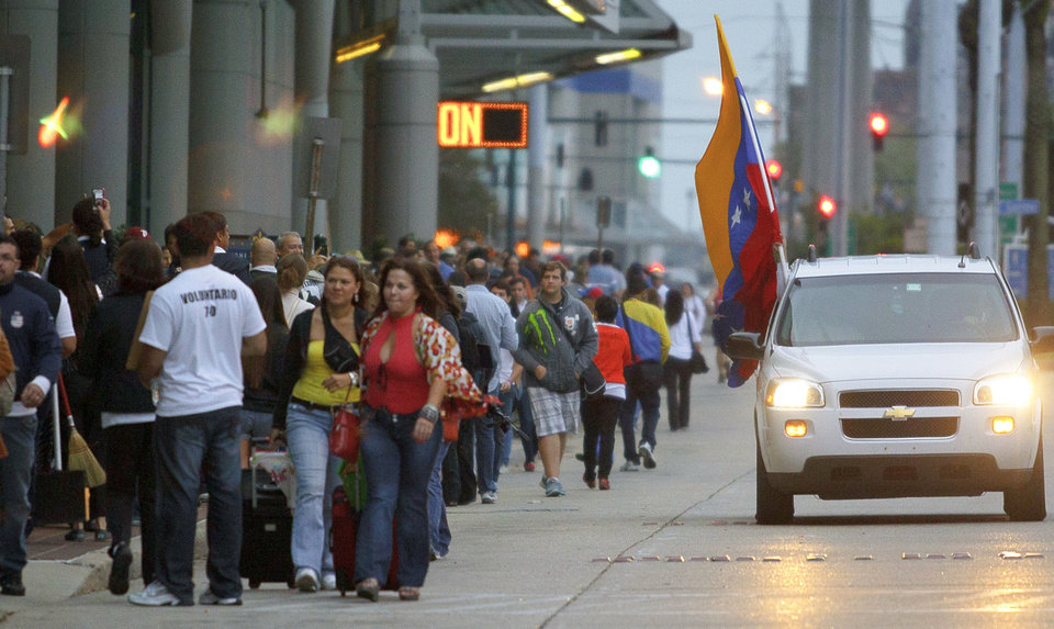 Venezuelan citizens living in the United States wait in line to vote at the New Orleans Ernest Morial Convention Center, in New Orleans, Sunday, Oct. 7, 2012. Hundreds of Venezuelans living in the U.S. streamed into New Orleans on Sunday to cast ballots in the presidential election in their homeland, many of them determined to end the 13-year reign of Hugo Chavez. With the country's consulate in Miami closed, thousands of Venezuelans traveled by bus, car and plane to cast their votes at the consulate in New Orleans. (AP Photo/Matthew Hinton)