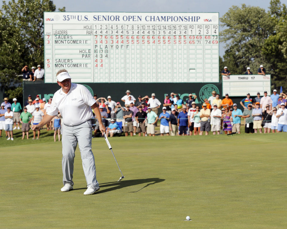 Photo - Colin Montgomerie watches his winning putt on No. 18 in a third playoff hole during the final round of the U.S. Senior Open golf tournament at Oak Tree National in Edmond, Okla., Sunday, July 13, 2014. Photo by Nate Billings, The Oklahoman