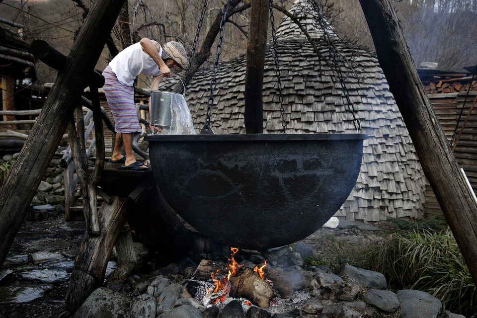 Photo - Bathhouse worker Alexander Bogatov prepares a hot pot at the British Banya bathhouse, Saturday, Feb. 15, 2014, in Krasnaya Polyana, Russia. Preparations begin late in the afternoon, at least three hours before the bathing party arrives. (AP Photo/Jae C. Hong)