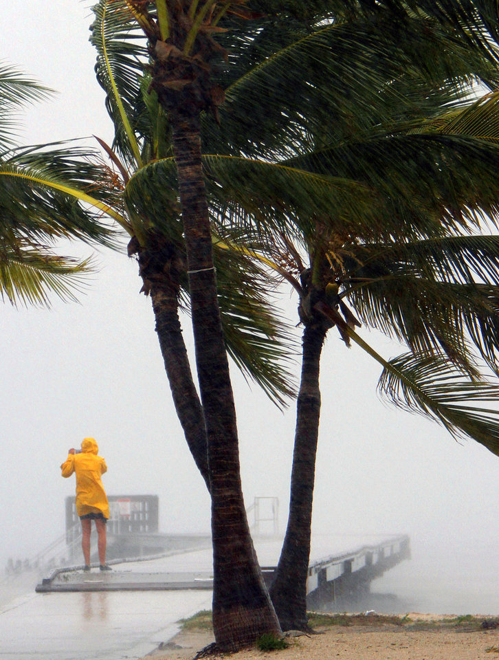 A person braves the rain at Clarence Higgs Beach in Key West, Fla., as Tropical Storm Isaac hits the area on Sunday, Aug. 26, 2012. Isaac gained fresh muscle Sunday as it bore down on the Florida Keys, with forecasters warning it could grow into a dangerous Category 2 hurricane as it nears the northern Gulf Coast. (AP Photo/The Miami Herald, Walter Michot) ORG XMIT: FLMIH106