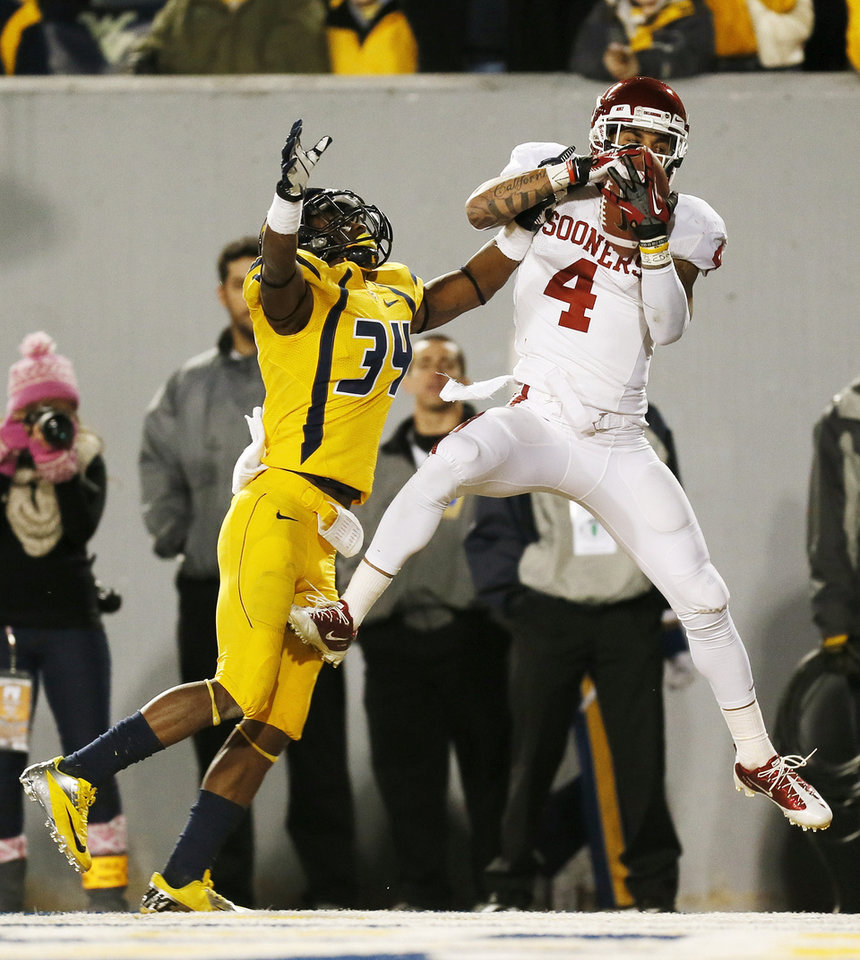 Photo - Oklahoma's Kenny Stills (4) catches a pass for a touchdown in the third quarter against West Virginia's Ishmael Banks (34) during a college football game between the University of Oklahoma and West Virginia University on Mountaineer Field at Milan Puskar Stadium in Morgantown, W. Va., Nov. 17, 2012. OU won, 50-49. Photo by Nate Billings, The Oklahoman