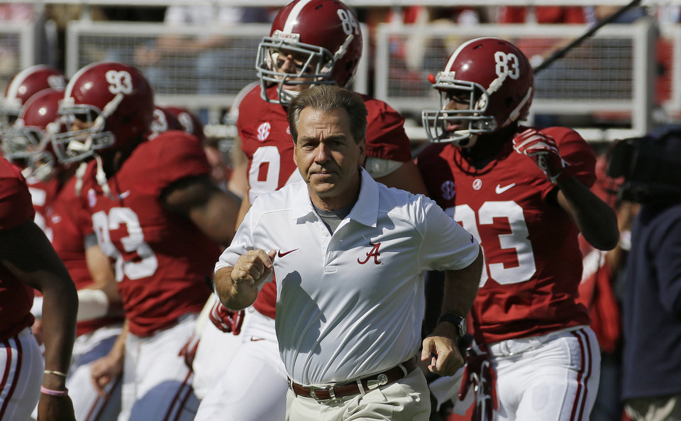 Photo - Alabama head coach Nick Saban leads his team on to the field for an NCAA college football game against Tennessee in Tuscaloosa, Ala., Saturday, Oct. 26, 2013. (AP Photo/Dave Martin)