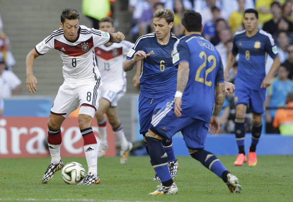 Photo - Germany's Mesut Ozil, left, controls the ball as Argentina's Ezequiel Lavezzi, right, and Argentina's Lucas Biglia (6) watch him, during the World Cup final soccer match between Germany and Argentina at the Maracana Stadium in Rio de Janeiro, Brazil, Sunday, July 13, 2014. (AP Photo/Victor R. Caivano)
