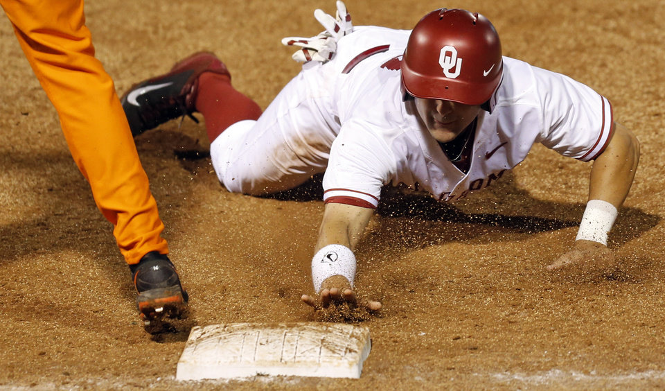 Photo - OU's Anthony Hermelyn (9) gets back to first base to avoid being picked off in the fourth inning during a Bedlam college baseball game between Oklahoma and Oklahoma State in the Big 12 baseball tournament at the Chickasaw Bricktown Ballpark in Oklahoma City,  Friday, May 23, 2014. Photo by Nate Billings, The Oklahoman