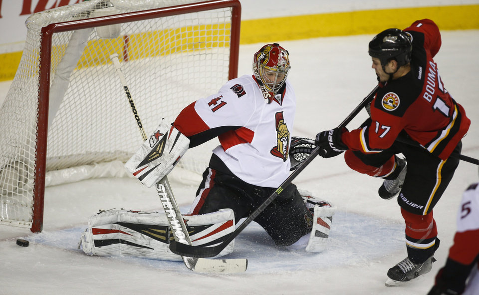 Photo - Ottawa Senators goalie Craig Anderson, left, kicks away a shot from Calgary Flames' Lance Bouma during third period NHL hockey action in Calgary, Alberta, Wednesday, March 5, 2014. The Calgary Flames beat the Ottawa Senators 4-1. (AP Photo/The Canadian Press, Jeff McIntosh)
