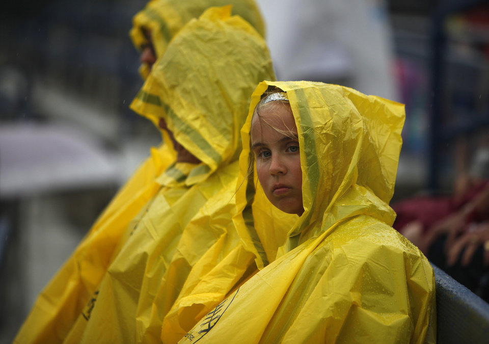 Madison Banister, 11, of Arkansas, sits in the rain with her family at ASA Hall of Fame Stadium in Oklahoma City, Wednesday, June 6, 2012.  The final game of the Women's World College Series was delayed due to weather conditions.  Photo by Garett Fisbeck, The Oklahoman
