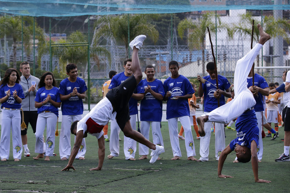 Photo - England national soccer team player Daniel Sturridge, front left, joins in a Capoeira dance demonstration with locals watched by his teammate Jack Wilshire, second left, during a visit to the Rocinha Sports Complex on the edge of the Rocinha favela in Rio de Janeiro, Brazil, Monday, June 9, 2014.  The England soccer team are staying in Rio de Janeiro as their base city for the 2014 soccer World Cup.  (AP Photo/Matt Dunham)