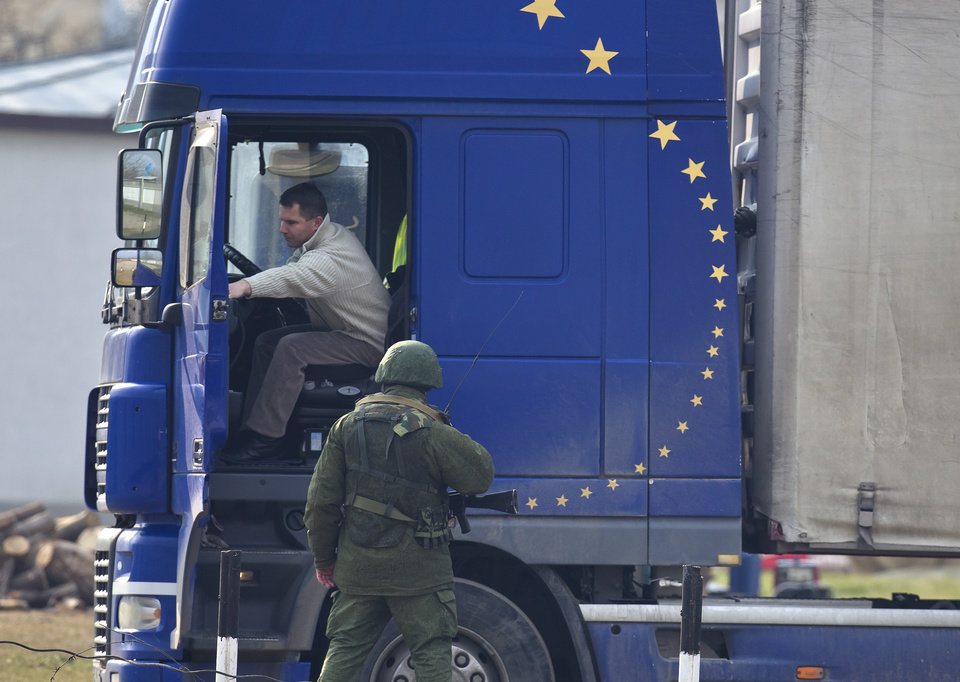Photo - A pro-Russian soldier speaks to a truck driver outside the Ukrainian infantry base in Perevalne, Ukraine, Wednesday, March 12, 2014. The Group of 7 world leaders said in a statement released from the White House on Wednesday that they won't recognize results of a referendum for the Crimea region to split from Ukraine and join Russia.(AP Photo/Vadim Ghirda)