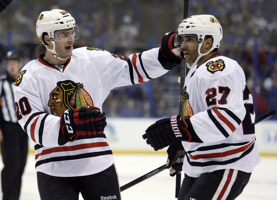 Photo - Chicago Blackhawks' Johnny Oduya, of Sweden, is congratulated by Brandon Saad, left, after scoring during the first period in Game 1 of a first-round NHL hockey Stanley Cup playoff series against the St. Louis Blues Thursday, April 17, 2014, in St. Louis. (AP Photo/Jeff Roberson)