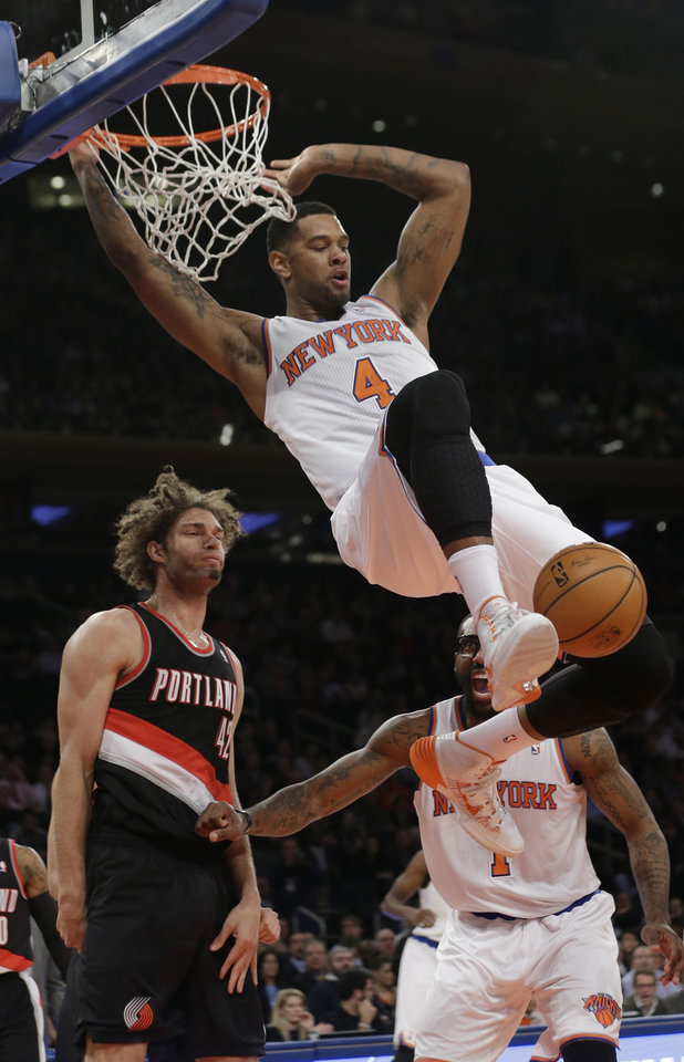 Photo - New York Knicks' Jeremy Tyler (4) dunks the ball in front of Portland Trail Blazers' Robin Lopez (42) during the first half of an NBA basketball game, Wednesday, Feb. 5, 2014, in New York. (AP Photo/Frank Franklin II)