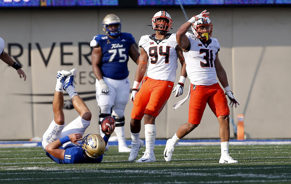 Photo - Oklahoma State's Kolby Harvell-Peel (31) celebrates a sack on Tulsa's Zach Smith (11) as Trace Ford (94) celebrates during a college football game between the Oklahoma State University Cowboys (OSU) and the University of Tulsa Golden Hurricane (TU) at H.A. Chapman Stadium in Tulsa, Okla., Saturday, Sept. 14, 2019. [Sarah Phipps/The Oklahoman]