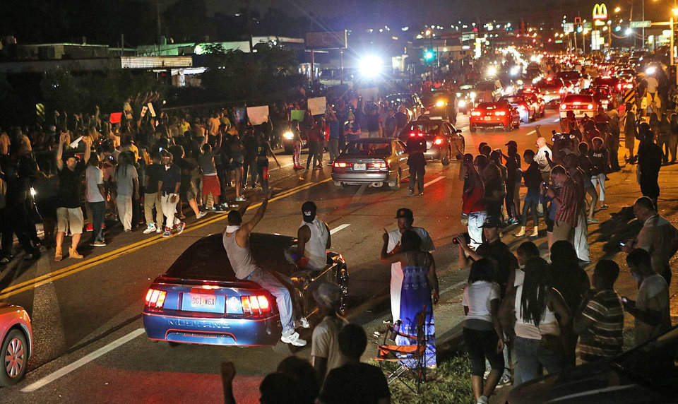 Photo - Many people drove down the street honking their horns, raising their arms, and holding signs on W. Florissant in Ferguson on Thursday evening, Aug. 14, 2014, as some demonstrators stood in the middle of the street. (AP Photo/St. Louis Post-Dispatch, J.B. Forbes)