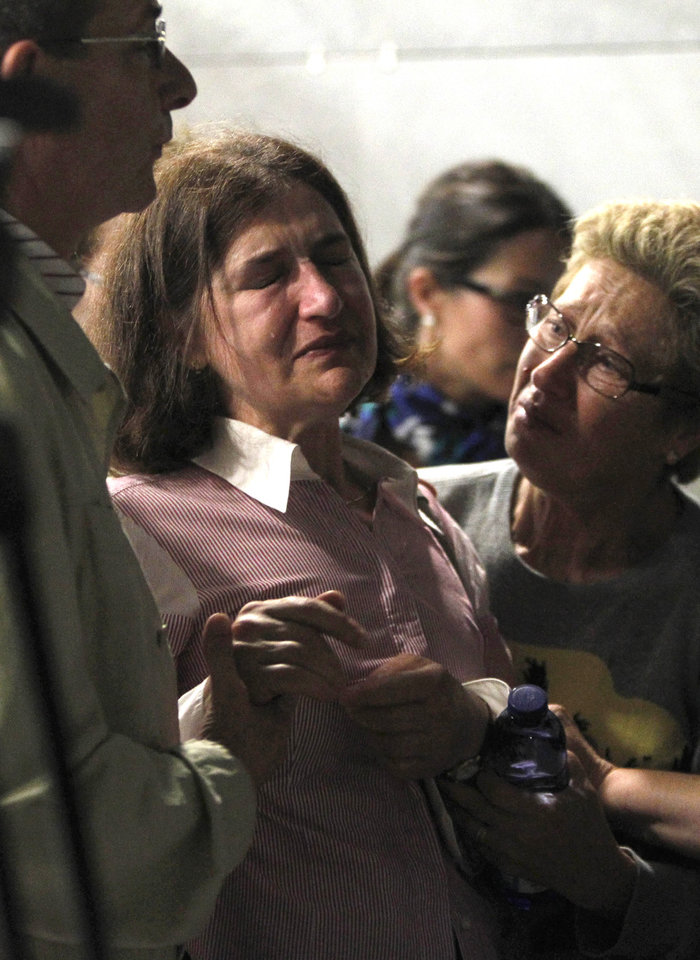 Photo - A woman reacts as relatives of victims of a train accident wait for news while gathering at an area where information will be released  in Santiago de Compostela, Spain, on Thursday, July 25, 2013. The death toll in a passenger train crash in northwestern Spain rose to 77 on Thursday after the train jumped the tracks on a curvy stretch just before arriving in the northwestern shrine city of Santiago de Compostela, a judicial official said. (AP Photo/ Salome Montes)