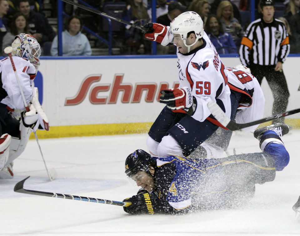 Photo - St. Louis Blues' T.J. Oshie (74) slides across the ice as he trips up Washington Capitals' Julien Brouillette (59) during the second period of an NHL hockey game, Tuesday, April 8, 2014, in St. Louis.(AP Photo/Tom Gannam)