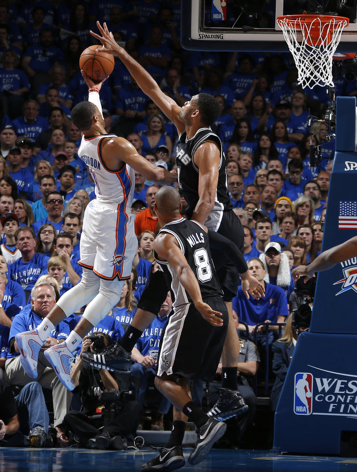 Photo - Oklahoma City's Russell Westbrook (0) goes to the basket as San Antonio's Patty Mills (8) and Tim Duncan (21) defend during Game 3 of the Western Conference Finals in the NBA playoffs between the Oklahoma City Thunder and the San Antonio Spurs at Chesapeake Energy Arena in Oklahoma City, Sunday, May 25, 2014. Photo by Bryan Terry, The Oklahoman
