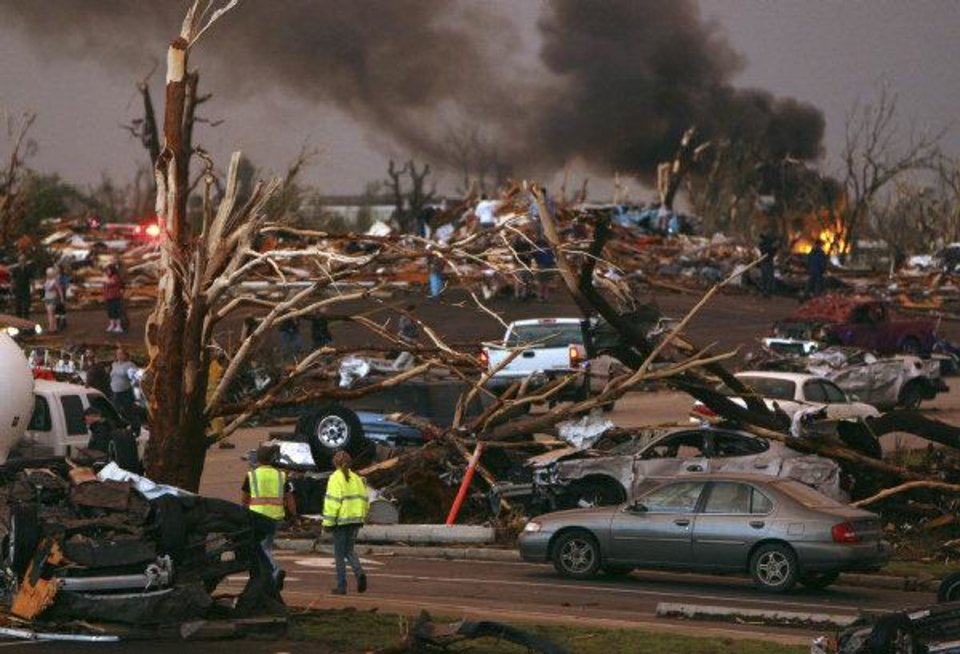 Emergency personnel walk through a neighborhood severely damaged by a tornado near the Joplin Regional Medical Center in Joplin, Mo., Sunday, May 22, 2011. A large tornado moved through much of the city, damaging a hospital and hundreds of homes and businesses. (AP Photo/Mark Schiefelbein) ORG XMIT: MOMS103