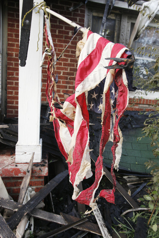 Photo - Burned American flag on the front porch of a fatal house fire at 2112 NW 20 Street in Oklahoma City Thursday, July 19, 2012. Photo by Paul B. Southerland, The Oklahoman