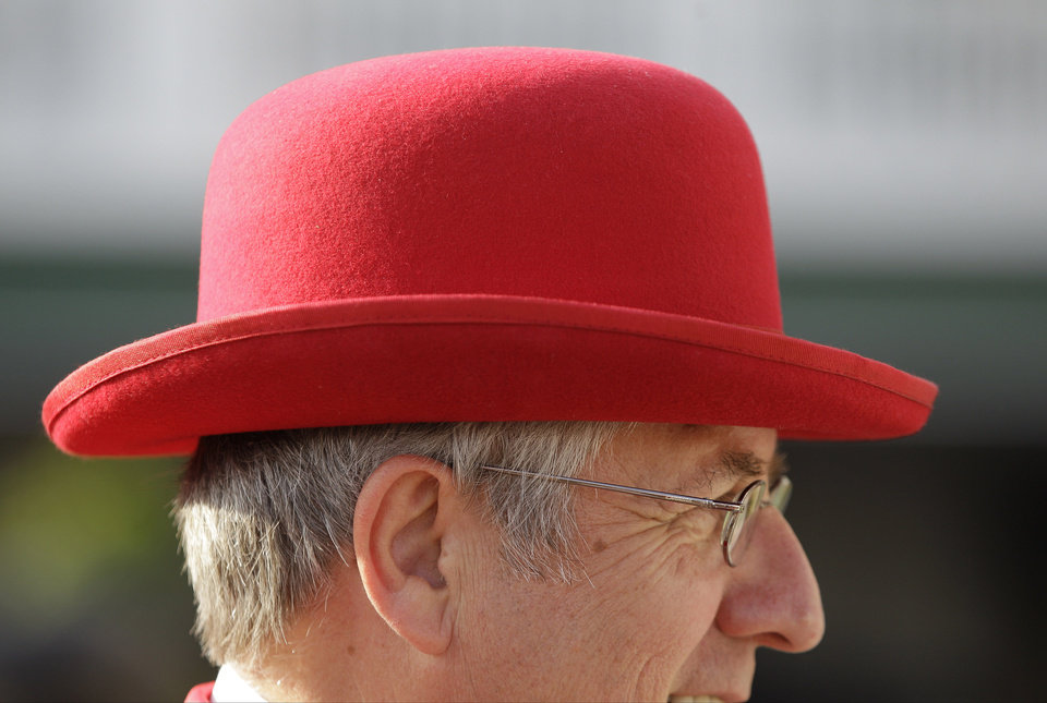 Jim Leuenberger, from Shawano, Wis., wears a red bowler hat white while walking through the paddock before the 138th Kentucky Derby horse race at Churchill Downs, Saturday, May 5, 2012, in Louisville, Ky. The Run for the Roses draws them to Churchill Downs. But what race goers wear is as much a spectacle in itself. (AP Photo/Mark Humphrey) ORG XMIT: NY222