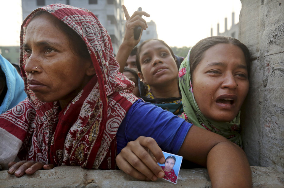 A Bangladeshi relative of a missing worker, right, cries as she holds his photo as they wait at the site of a building that collapsed Wednesday in Savar, near Dhaka, Bangladesh, Friday, April 26, 2013. The death toll reached hundreds of people as rescuers continued to search for injured and missing, after a huge section of an eight-story building that housed several garment factories splintered into a pile of concrete.(AP Photo/Kevin Frayer)