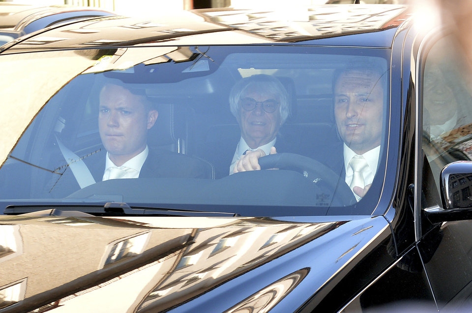 Photo - Bernie Ecclestone, center, the 83-year-old controlling business magnate in Formula One racing, sits in a car on his way to the regional court in Munich , Germany, Thursday, April 24, 2014. Ecclestone is charged with bribery and incitement to breach of trust