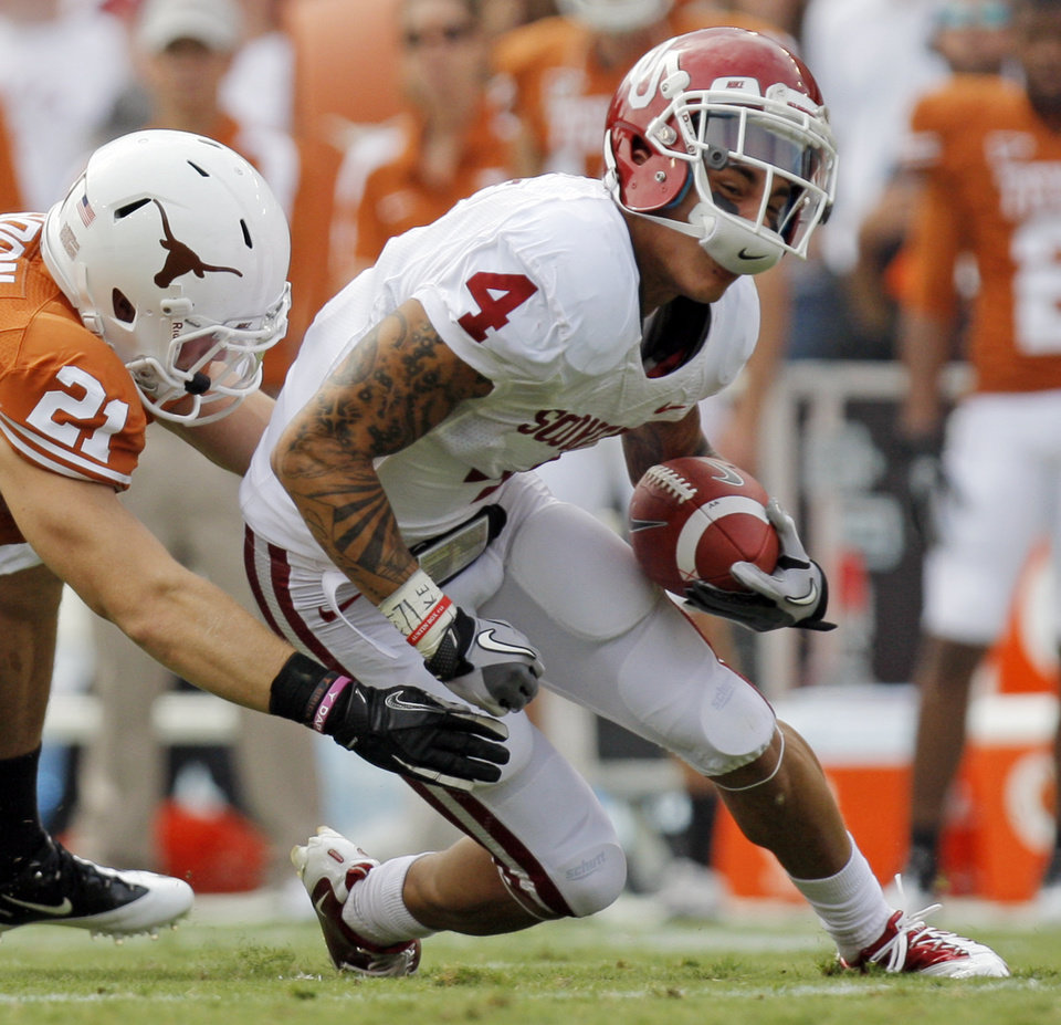 Photo - Blake Gideon (21) of Texas tackles Kenny Stills (4) of OU after a catch in the first half during the Red River Rivalry college football game between the University of Oklahoma Sooners (OU) and the University of Texas Longhorns (UT) at the Cotton Bowl in Dallas, Friday, Oct. 7, 2011. Photo by Nate Billings, The Oklahoman