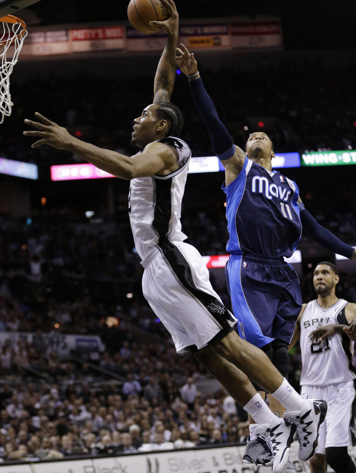 Photo - San Antonio Spurs' Kawhi Leonard, left, scores past Dallas Mavericks' Monta Ellis (11) during the first half of Game 5 of the opening-round NBA basketball playoff series on Wednesday, April 30, 2014, in San Antonio. (AP Photo/Eric Gay)